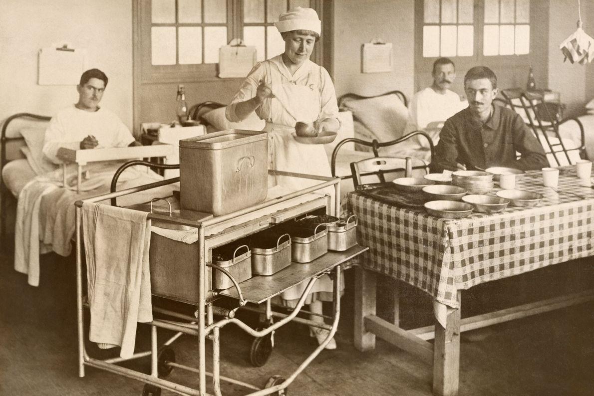 Una enfermera sirve comida a soldados estadounidenses heridos en un hospital en París, Francia, en 1918.