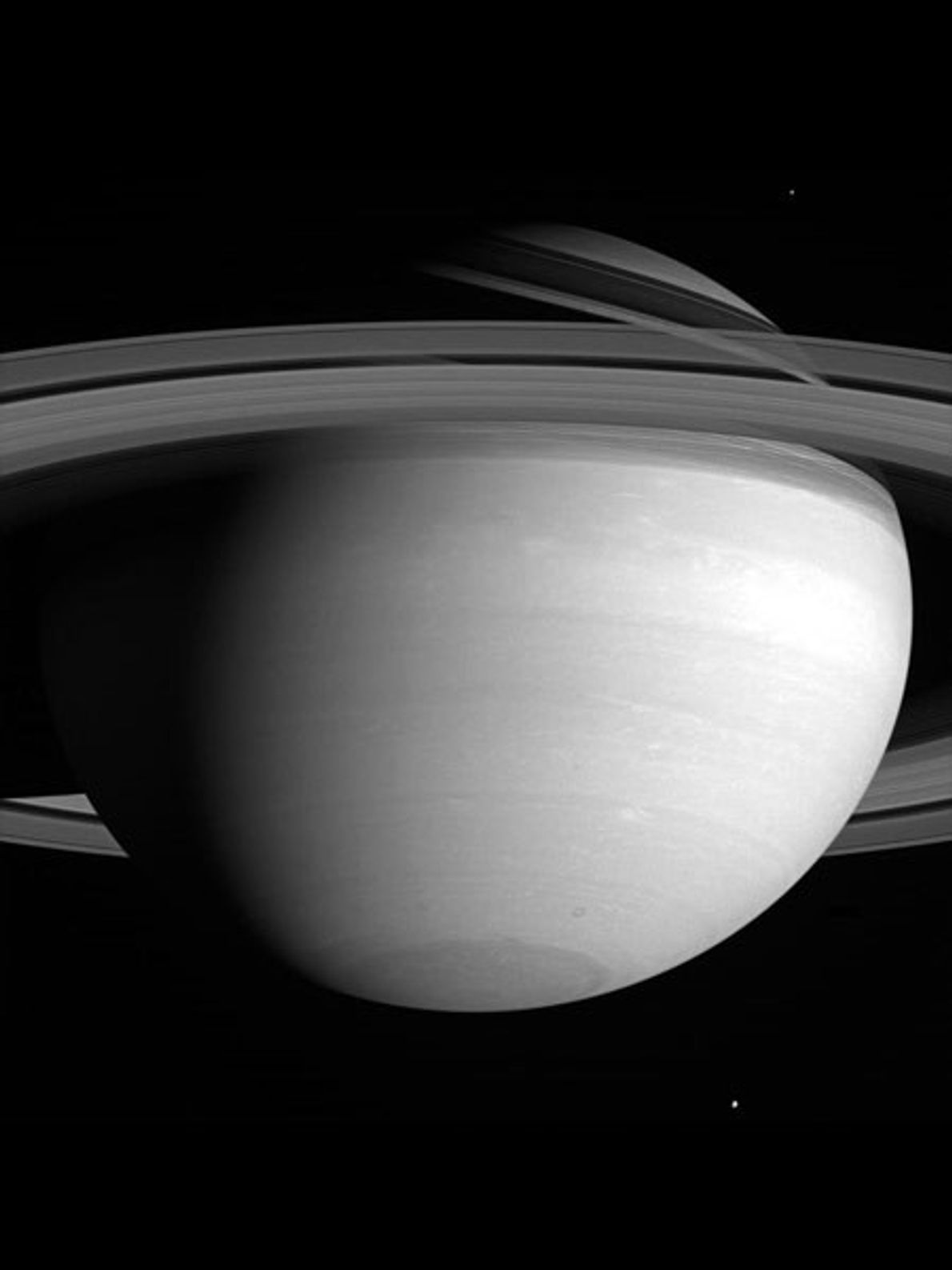 Dos de las más de 60 lunas conocidas de Saturno son prácticamente invisibles en esta imagen ...