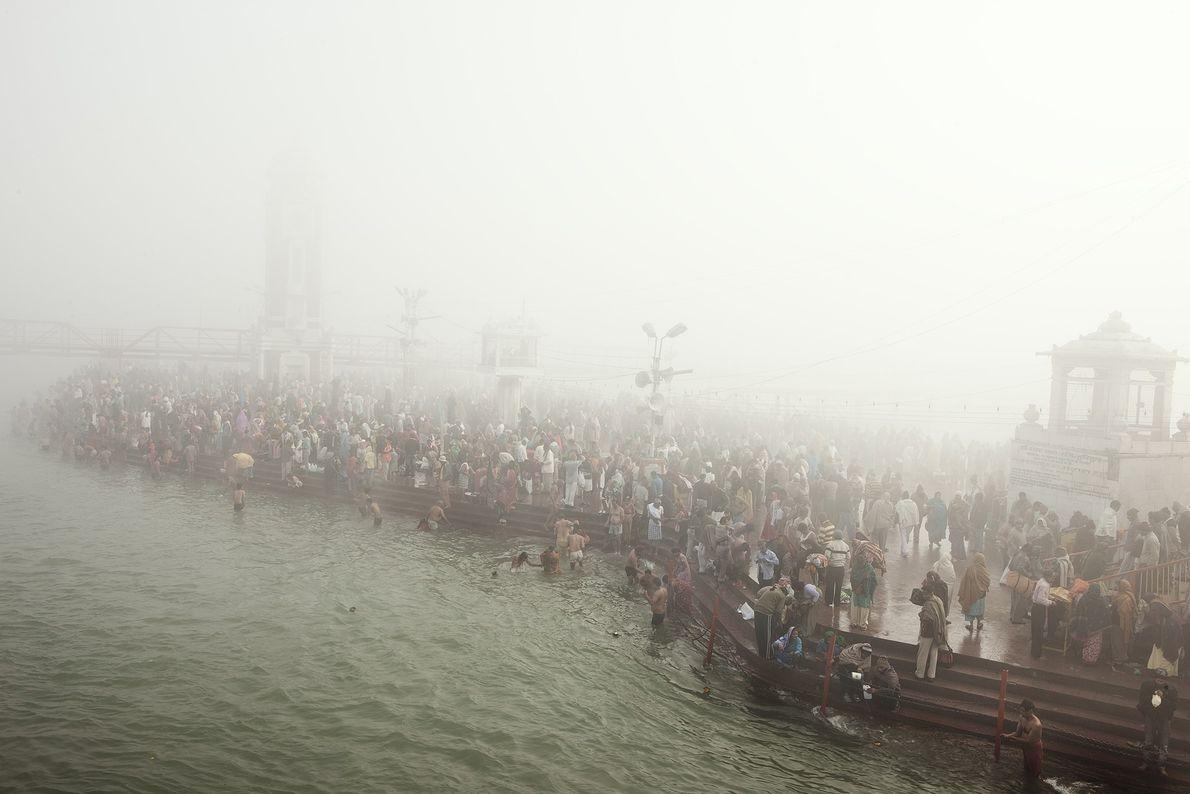 Devotos hindúes caminan por las aguas del Ganges para bañarse durante Kumbh Mela, India.