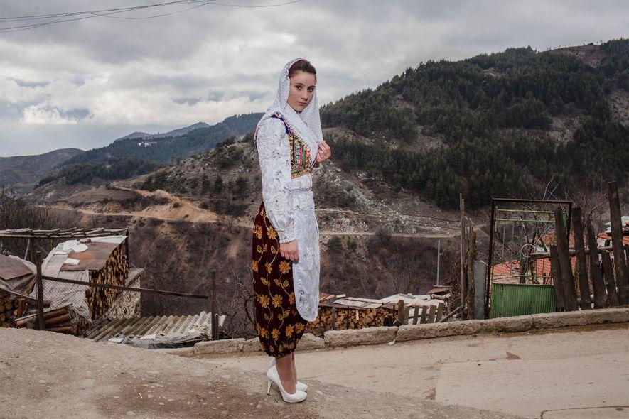 Vestida con el atuendo tradicional, una joven mujer en Ribnovo recorre su camino hacia la celebración ...