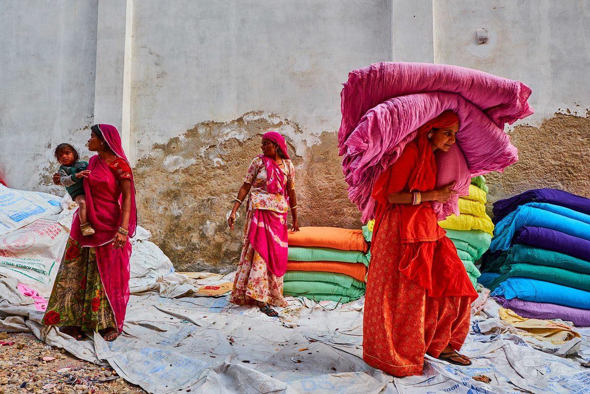 Las mujeres de Rajastán recogen saris recién secos en una fábrica. Antes de que se introdujeran ...