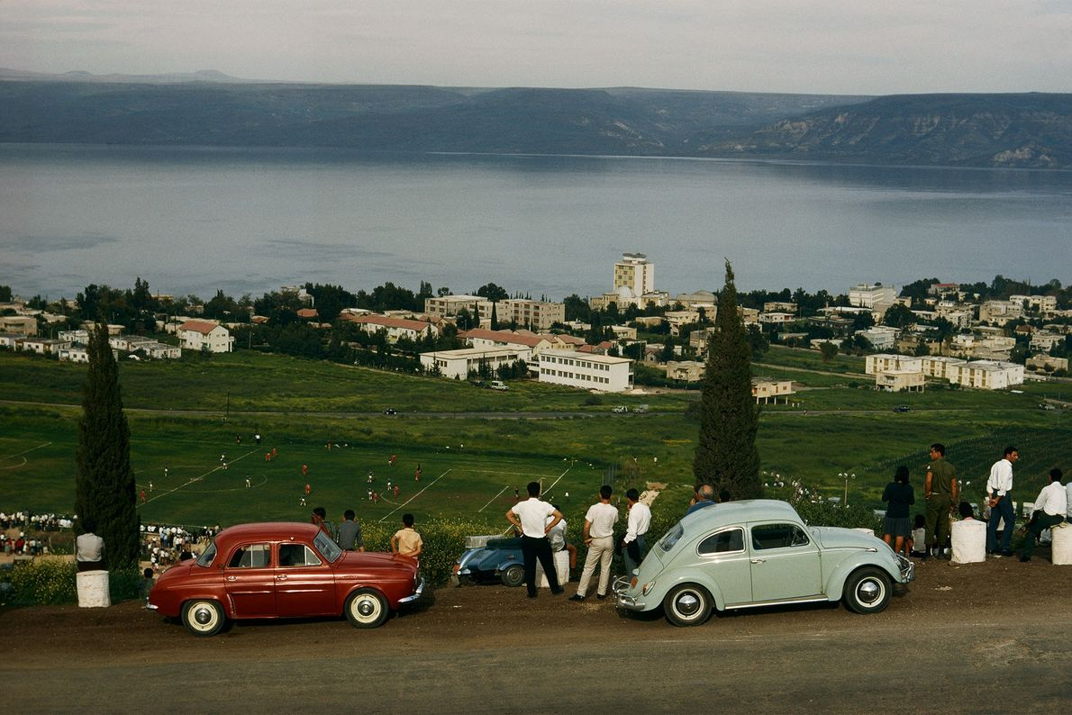 Turistas manejan sus autos cuesta arriba por la montaña y los estacionan allí para mirar el ...