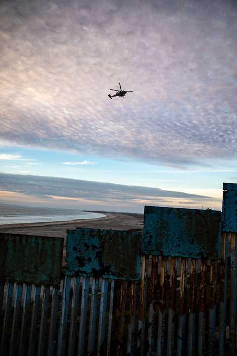 Unhelicópterodepatrullafronterizacirculasobrelaplayadondeunasecciónoxidadadela valla fronteriza se encuentra con el Océano Pacífico.