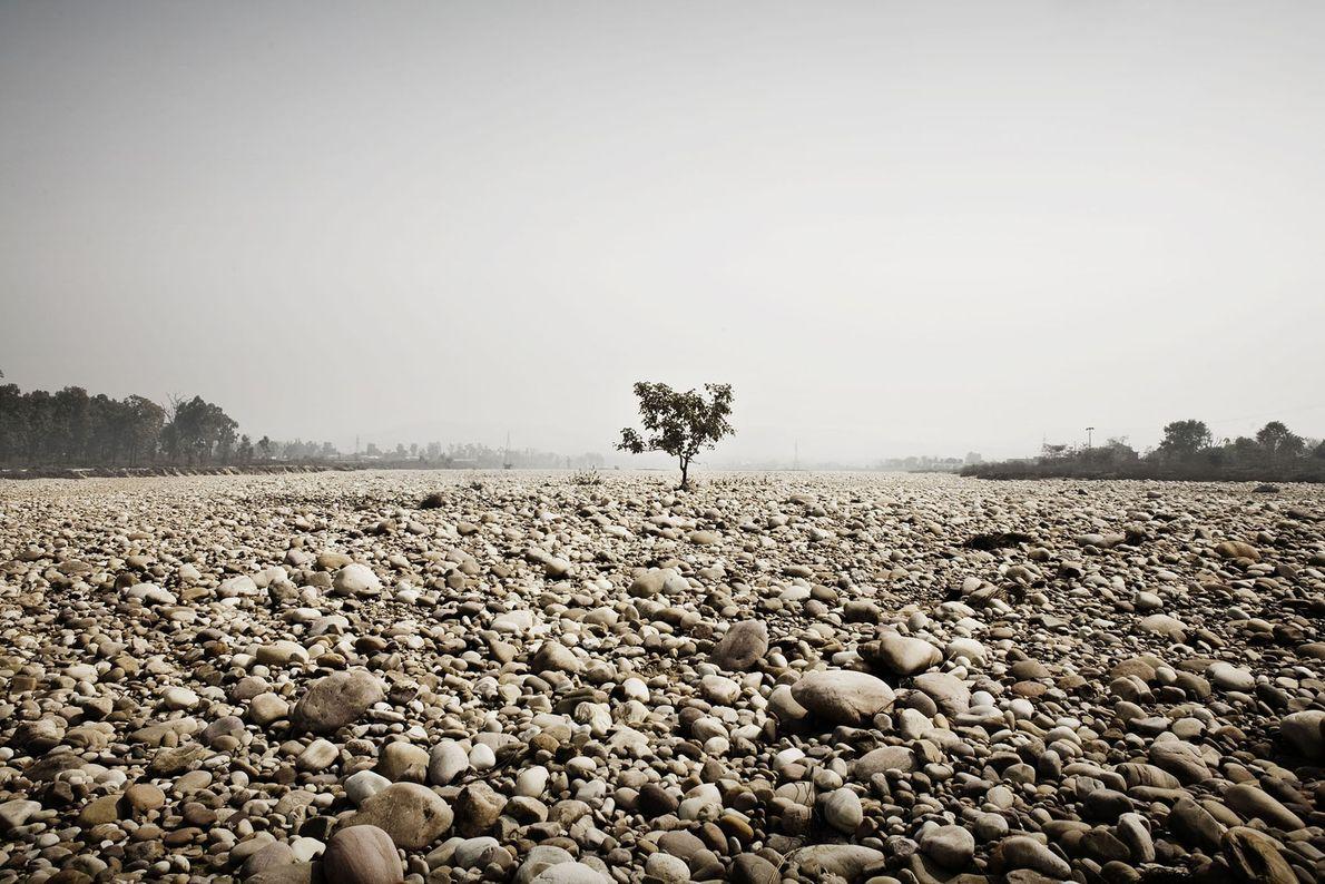 Uno de los afluentes del Ganges cerca de Haridwar cambia a árido y totalmente seco durante ...