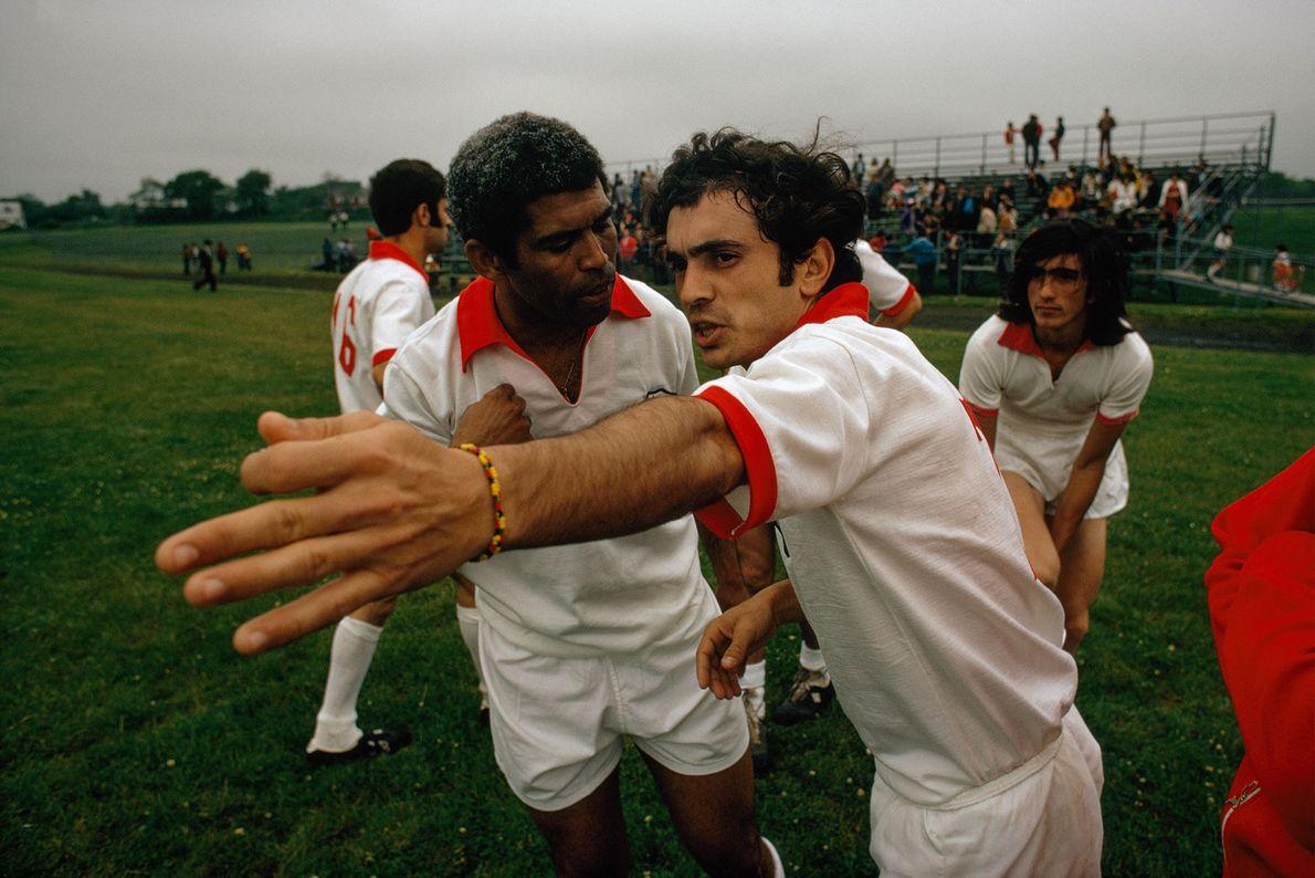 Un entrenador intenta calmar a un jugador del equipo que gesticula durante un partido de fútbol ...