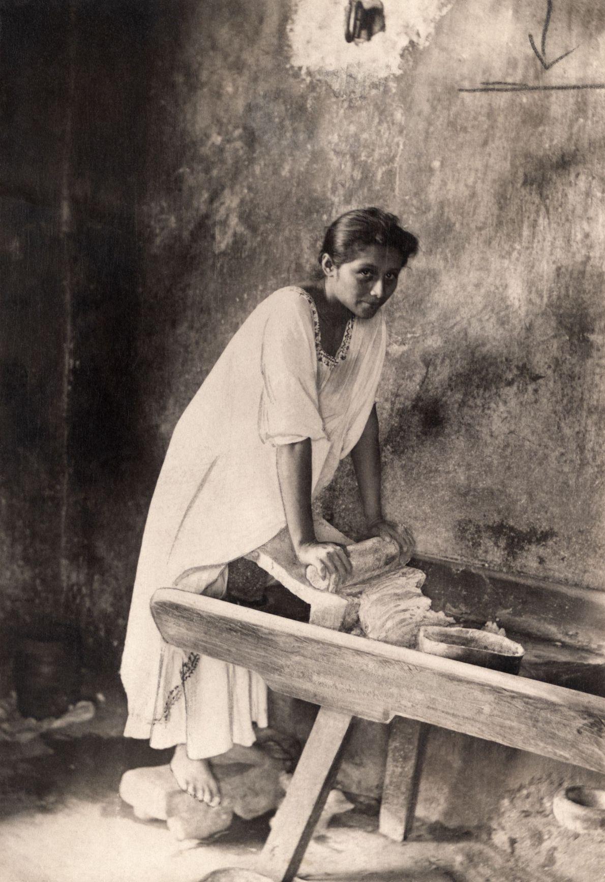 Una mujer posa en 1914 mientras muele maíz con un metate de piedra en México.