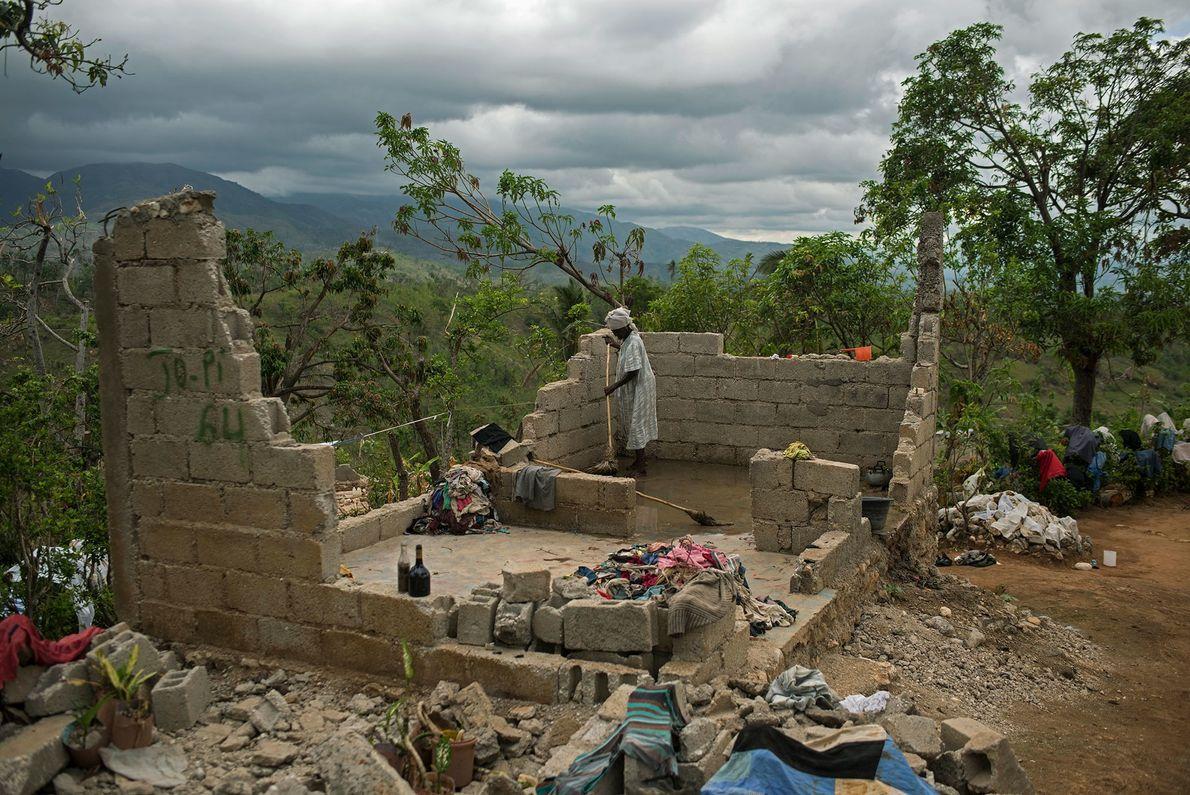 Una mujer intenta limpiar lo que queda de su casa en las montañas del sur de ...