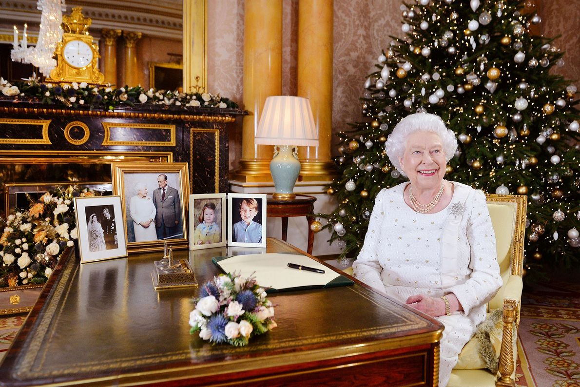 Se ve a la reina Isabel sentada en un escritorio del Salón 1844 del palacio de ...