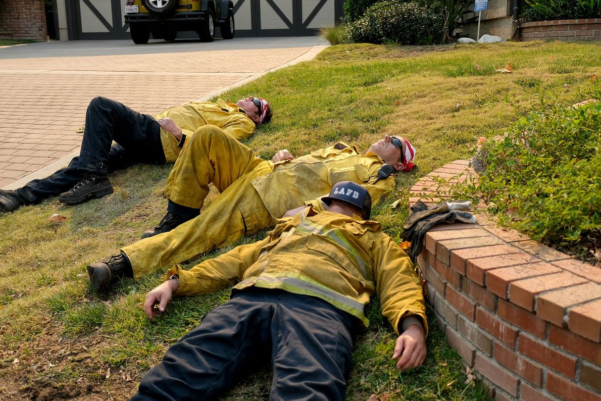 Los bomberos agotados descansan en Glenbridge Road en Westlake Village después de combatir el incendio de ...