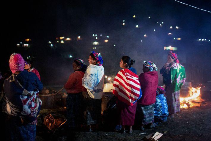 Las mujeres se envuelven en banderas en el velatorio de Mateo Pérez Marcos. Una banda tocaba ...