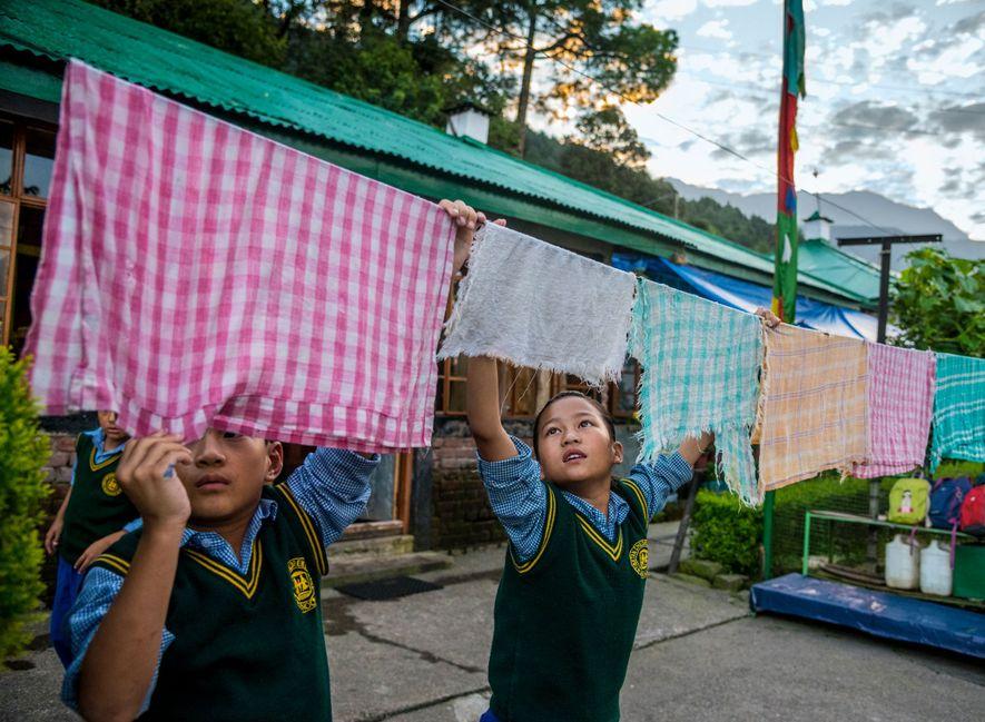 Niños tibetanos exiliados cuelgan la ropa antes de ir a la escuela en la aldea de ...