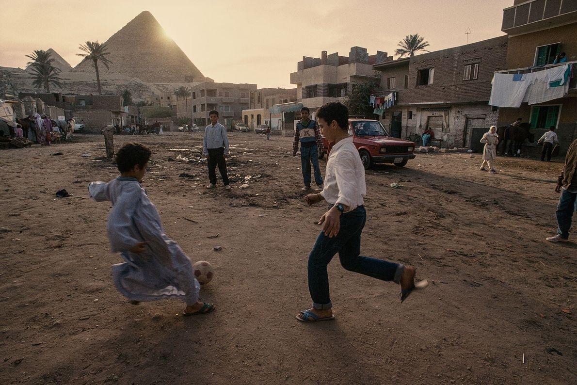 Niños de la aldea juegan al fútbol a los pies de las Pirámides de Giza en ...
