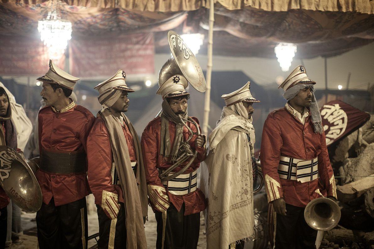 Un grupo de músicos se prepara para entretener a la multitud que está esperando por Sadhu, ...