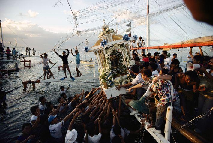 Los residentes fieles alcanzan un palanquín que contiene una imagen religiosa en Filipinas.