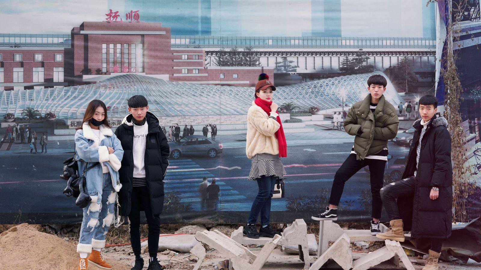 Estudiantes antes de rendir un examen de arte posan frente a unos afiches que promocionan Fushun, ...