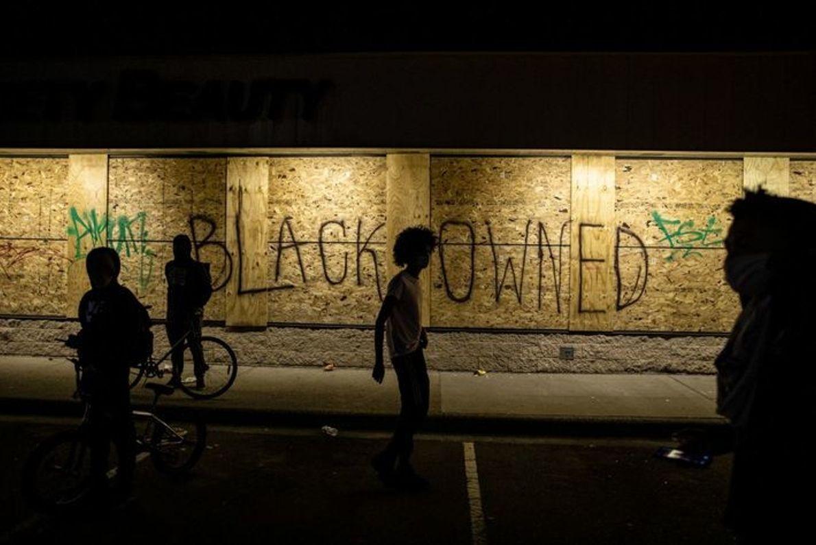 Una tienda tapiada con un mensaje que pide protección. Los manifestantes rompieron ventanas, saquearon y prendieron fuego ...
