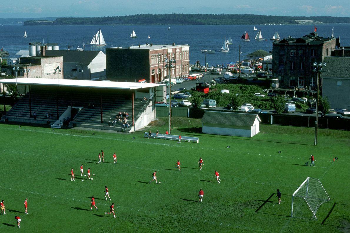 Jugadores participan de un partido de fútbol mientras los veleros pasan cerca durante el Festival de ...