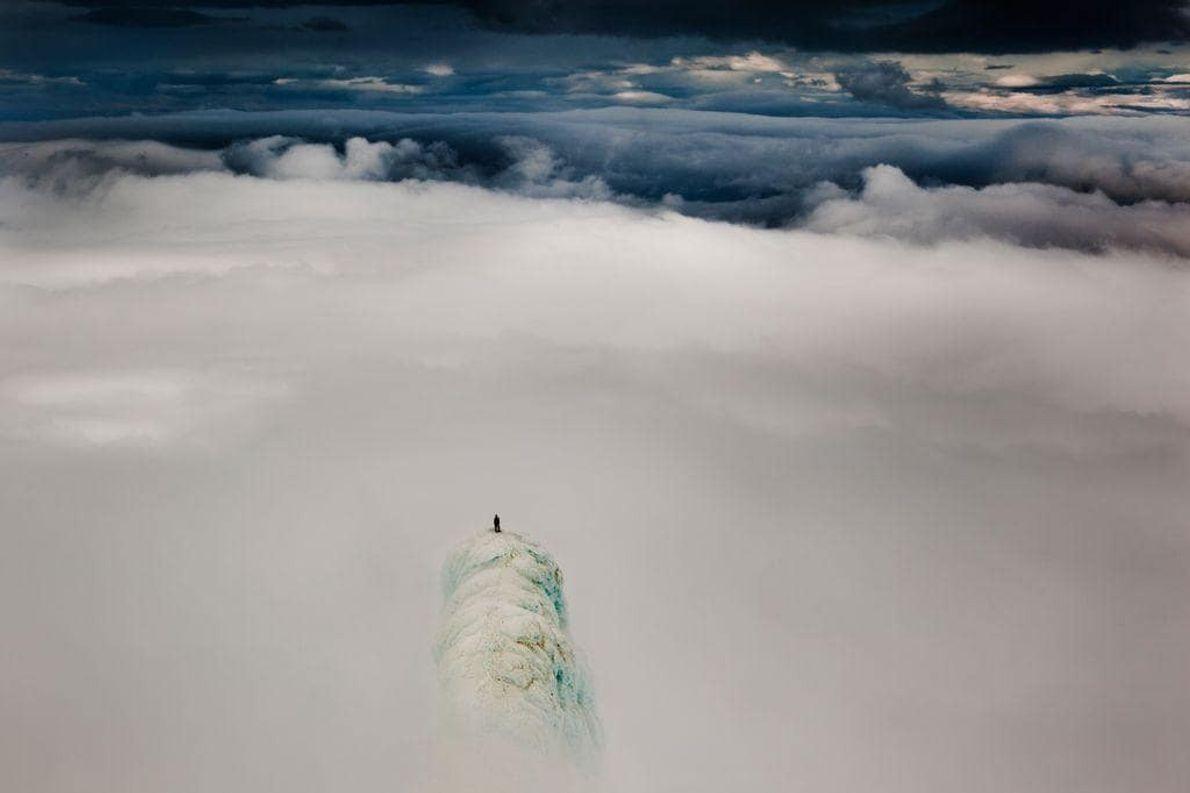 El escalador Remi McMurty sobresale sobre las nubes en dos de los pináculos de la cima ...
