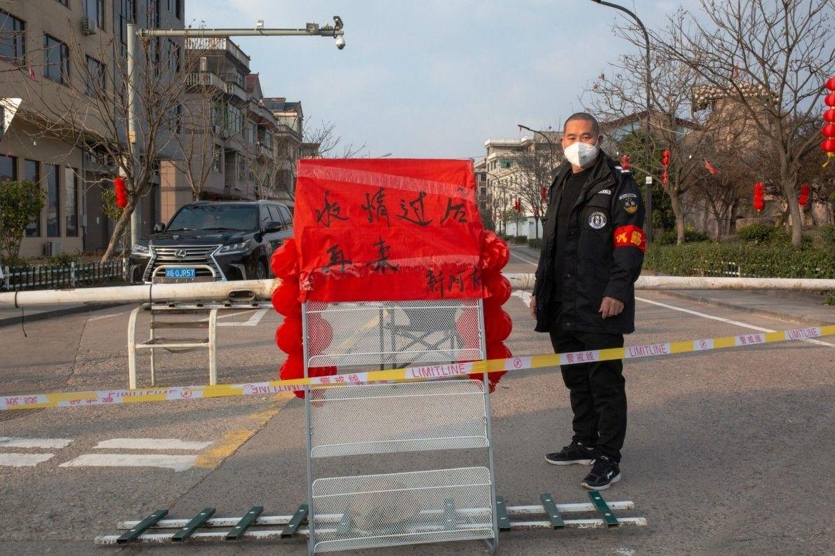 """La aldea de Xinhe colocó barricadas con cinta, postes telefónicos y una señal que dice: """"Vuelva ..."""