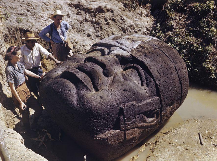 Los arqueólogos estudian una colosal cabeza de piedra olmeca en La Venta, México, en esta foto ...