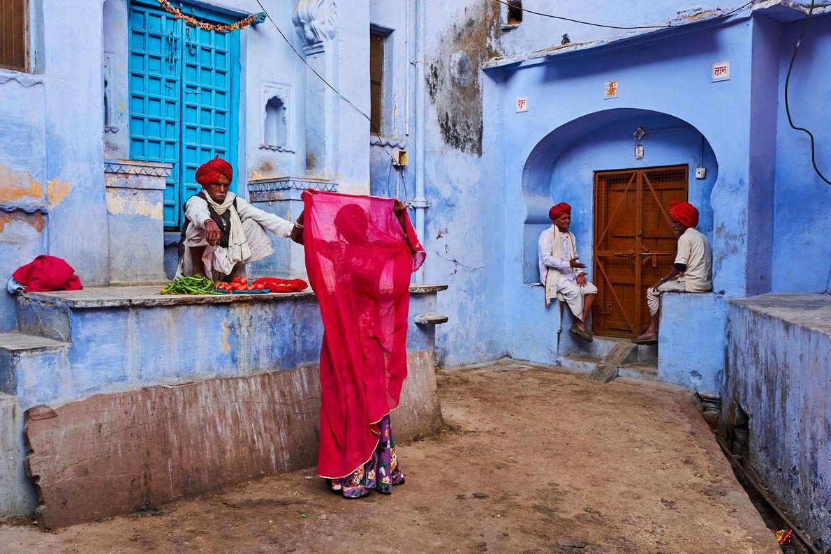 En Jodhpur, Rajasthan, el dupatta (chal) carmesí de una mujer contrasta con las paredes color pastel ...