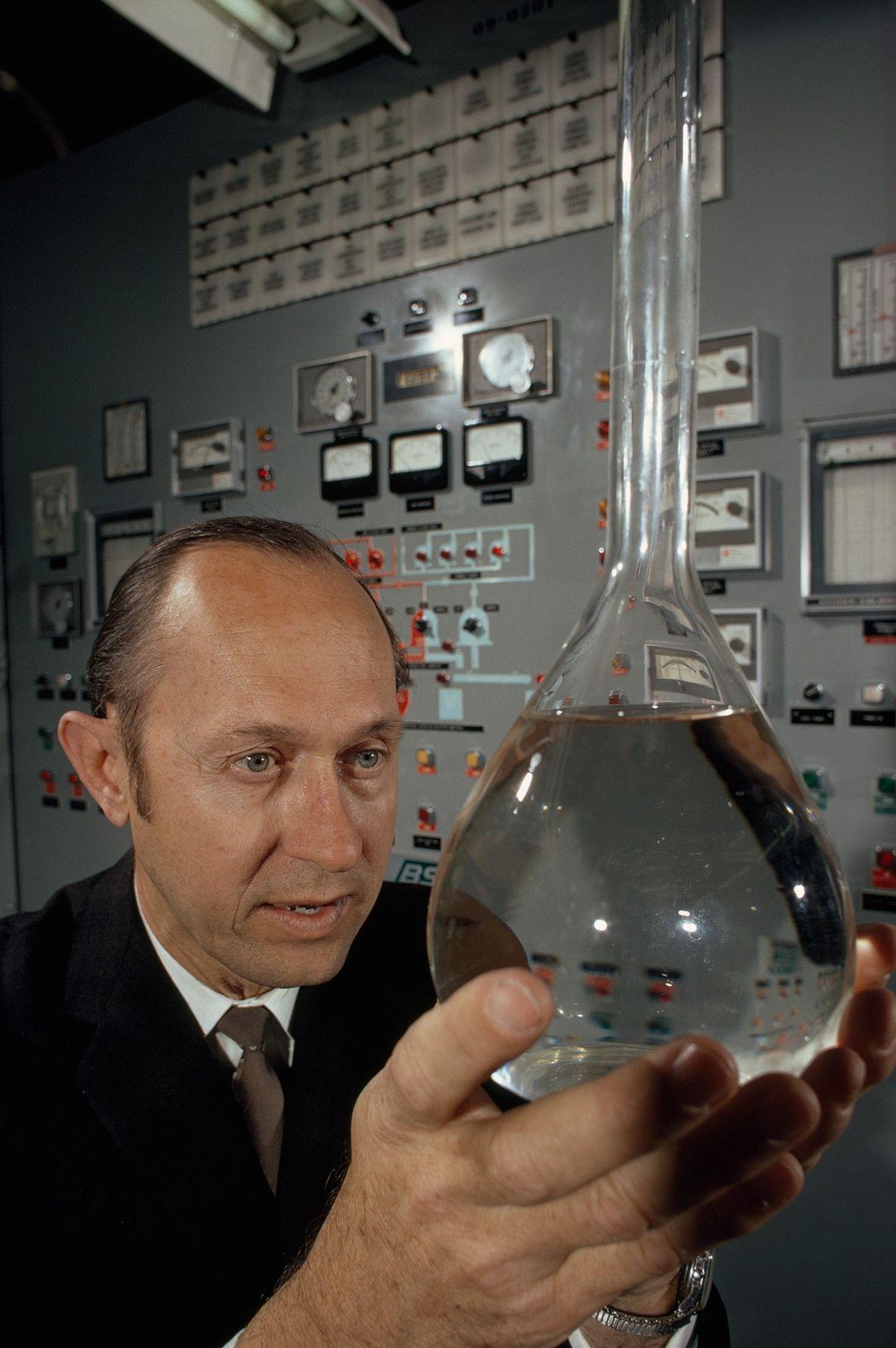 Un ingeniero sostiene una botella de agua limpia hecha de aguas residuales en 1970. Después de ...