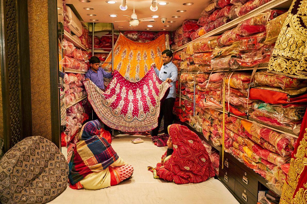 Las mujeres compran saris en una tienda en Jaipur apilados del piso al techo. La compra ...