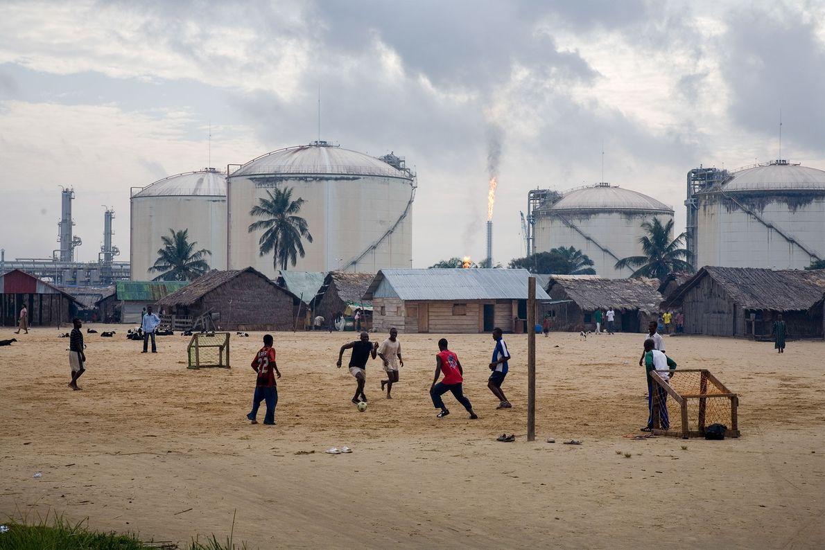 Jóvenes juegan al fútbol frente a unos tanques de almacenamiento de gas en la isla Bonny, ...