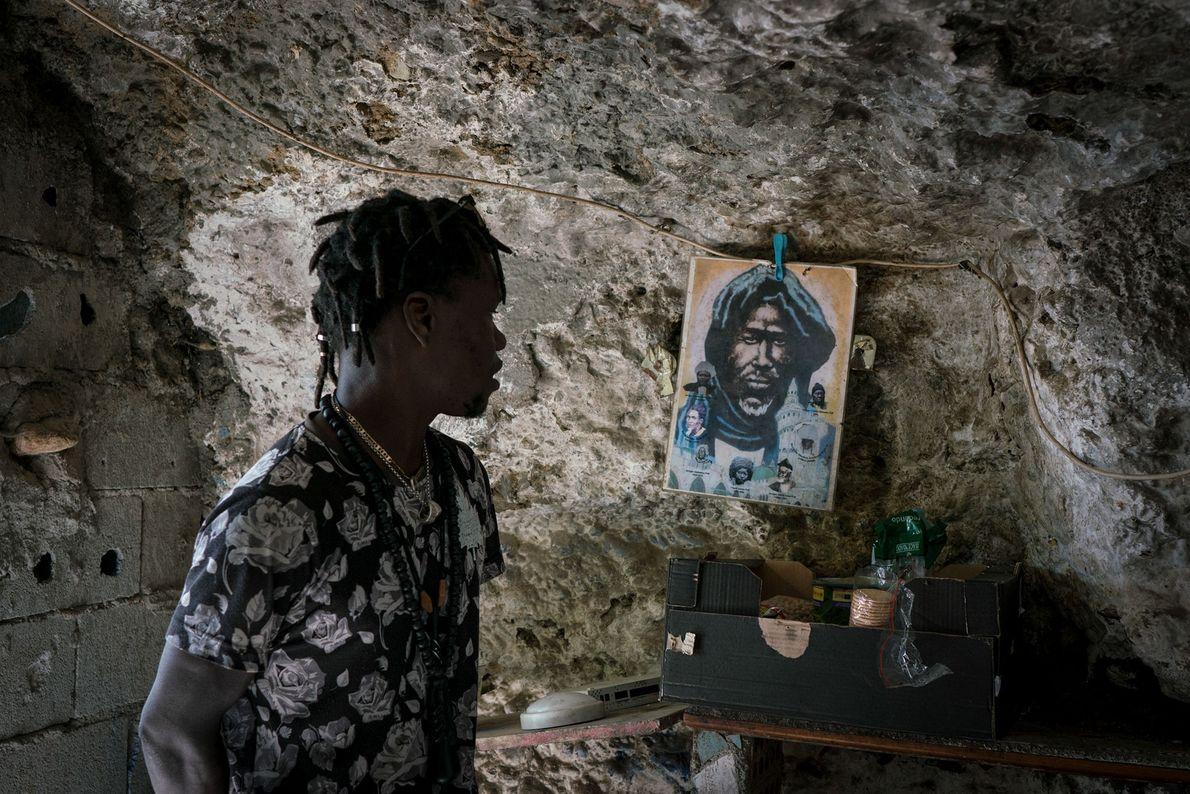 Malik, un inmigrante senegalés, mira una imagen que ha colgado en una pared de su cueva, ...