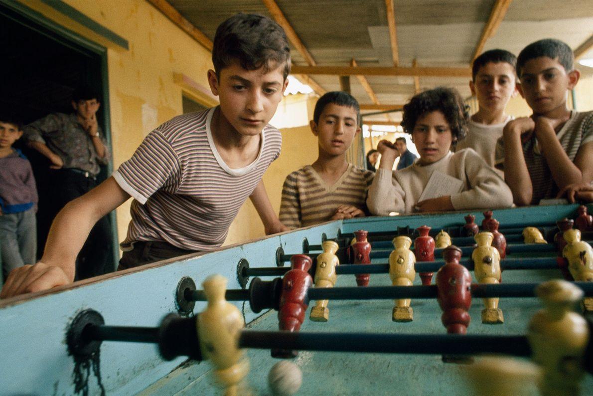 Estos niños refugiados juegan al fútbol de mesa, también conocido como metegol o futbolín, en un ...