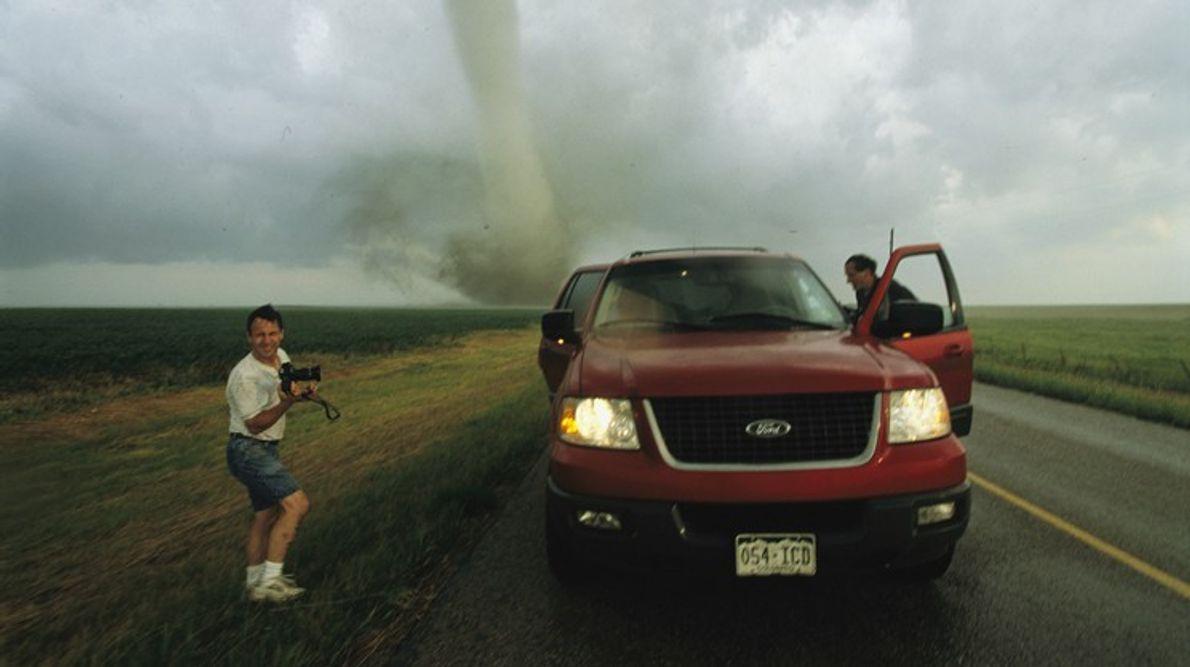 Un cazador de tornados con una cámara posa mientras su compañero se sube a su camión ...