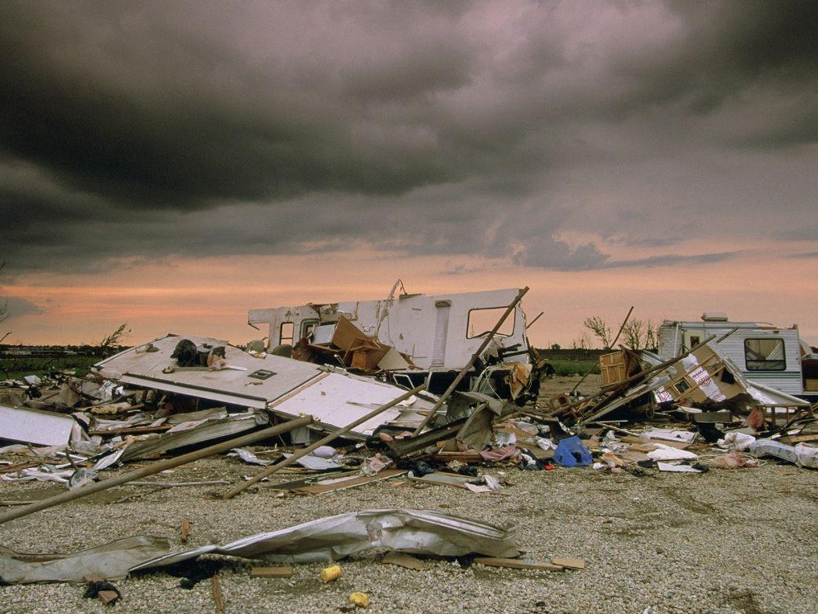 Cielos manchados por la tormenta se posan sobre los restos de una casa móvil demolida por ...