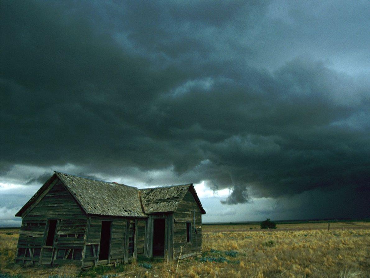 Nubes pesadas se encuentran bajas sobre una granja en el medio oeste, prediciendo un posible tornado. ...