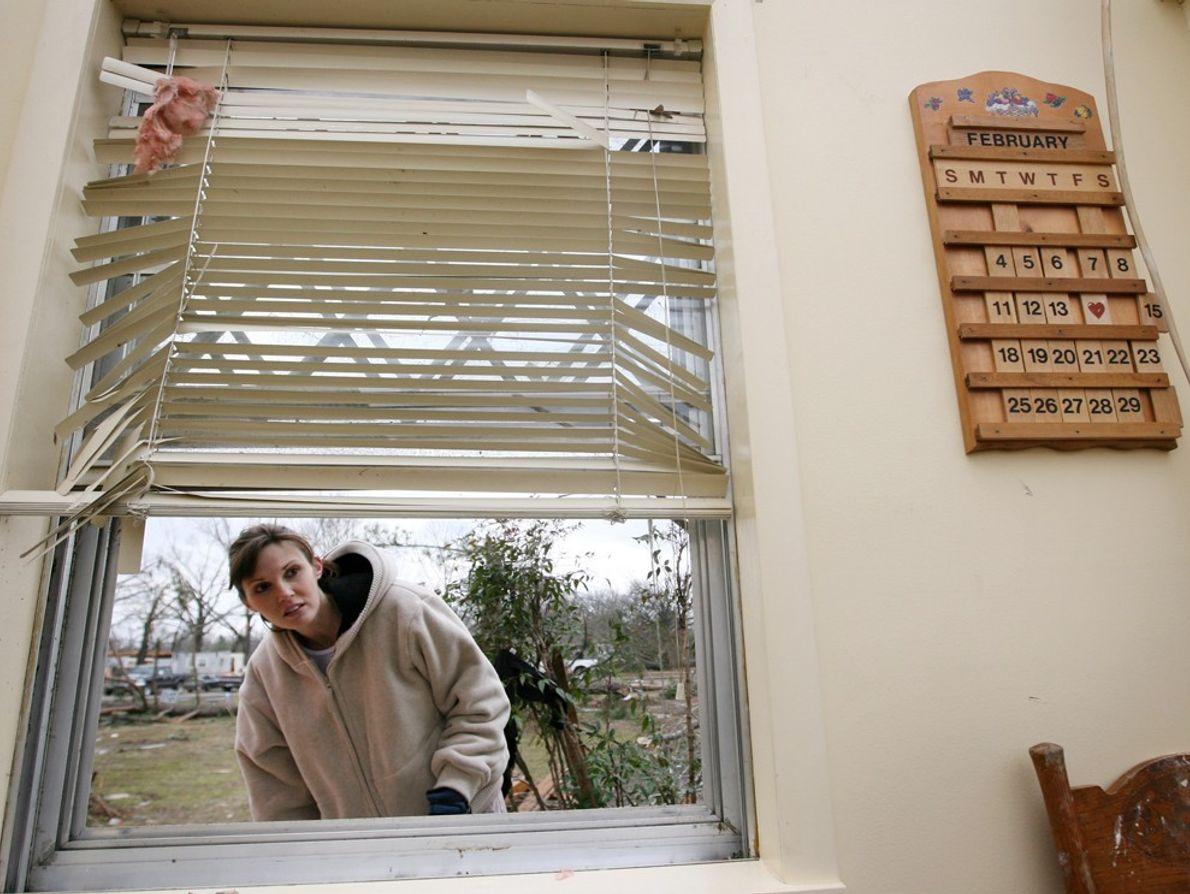 Una mujer mira a través de una ventana rota de la casa de un amigo después ...