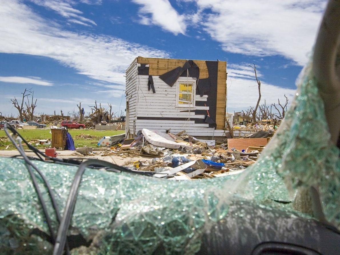 Una ventana rota de vidrio de seguridad de una casa destruida después de que un tornado ...