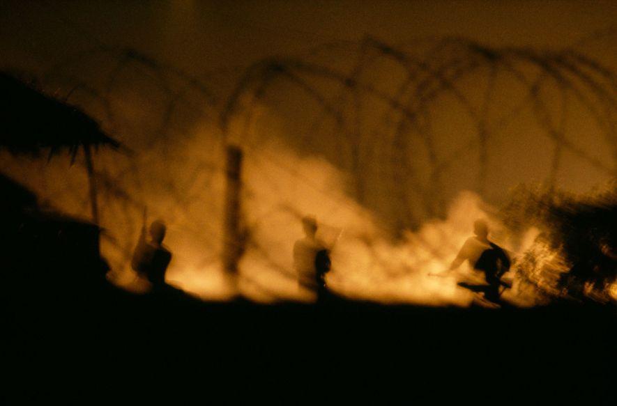 Un infierno llameante arroja a los soldados del Viet Cong de una cabaña en la noche ...