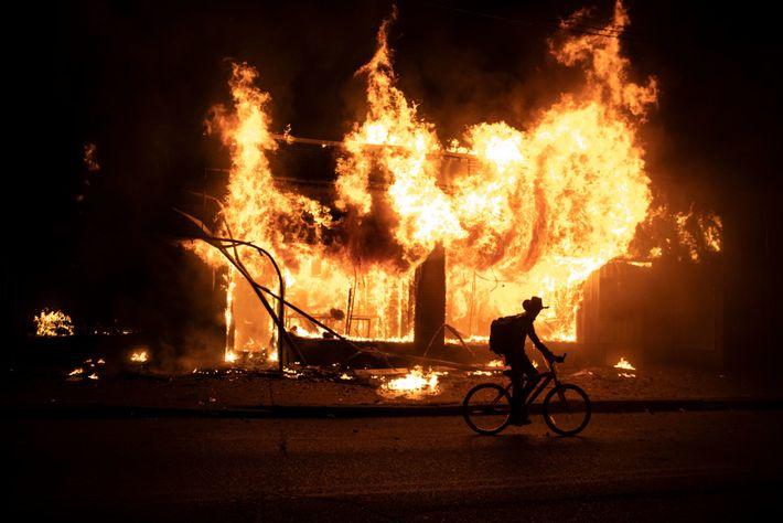 Un manifestante en bicicleta pasa frente a un edificio en llamas durante las protestas por la ...