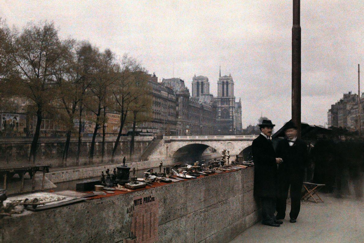 Dos hombres están parados junto a las baratijas en venta a orillas del Sena en la ...