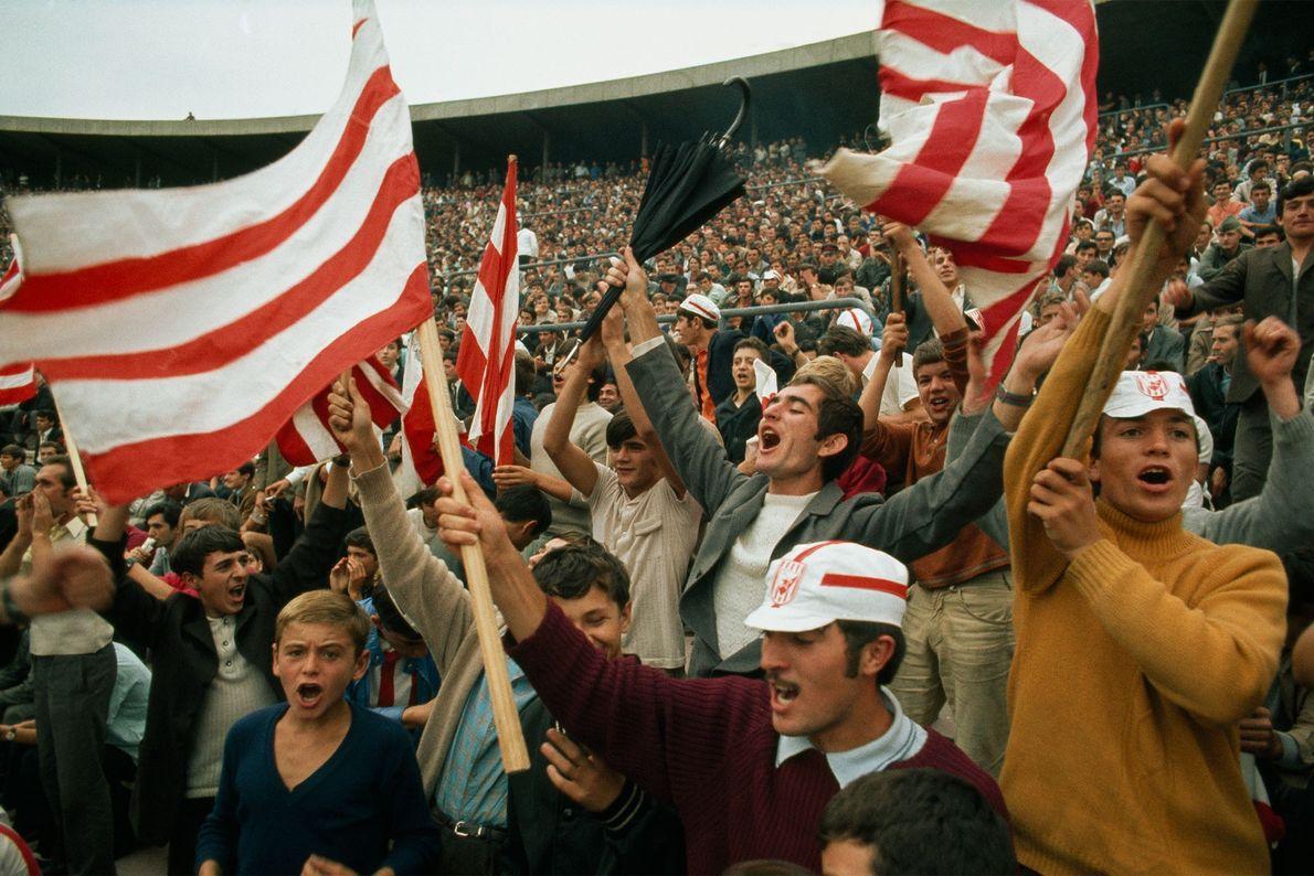 Durante un partido de fútbol en 1970 en Serbia, Yugoslavia, las fanáticos festejan un gol de ...