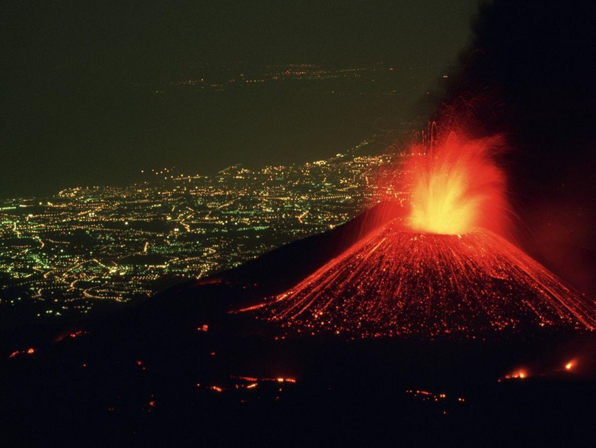 Situado en la iluminada ciudad de Catania, Italia, el Etna arroja hacia el cielo una fuente ...