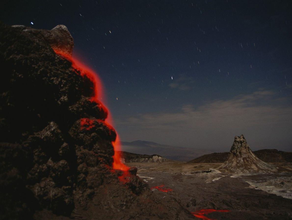 Una corriente de lava naranja fluorescente cae en cascada por Ol Doinyo Lengai, en el Gran ...
