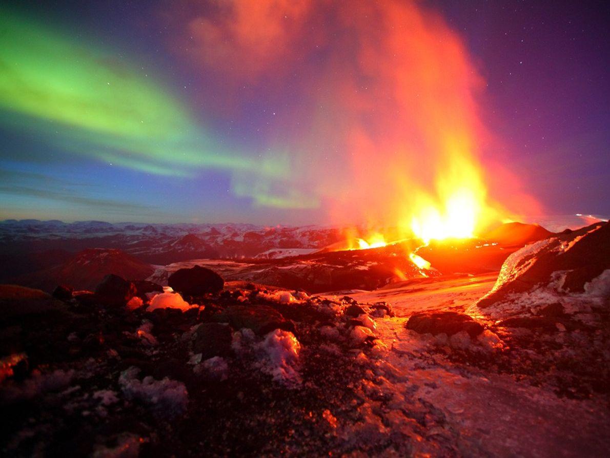 Auroras en el cielo durante una erupción volcánica en Islandia. La nación isleña es producto de ...