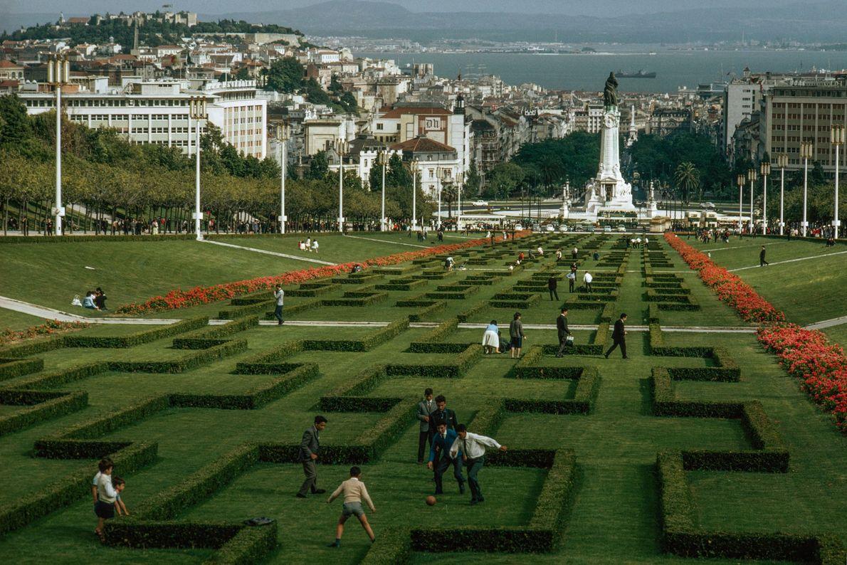 La gente da un paseo por un jardín labrado en Lisboa, Portugal, mientras un grupo de ...