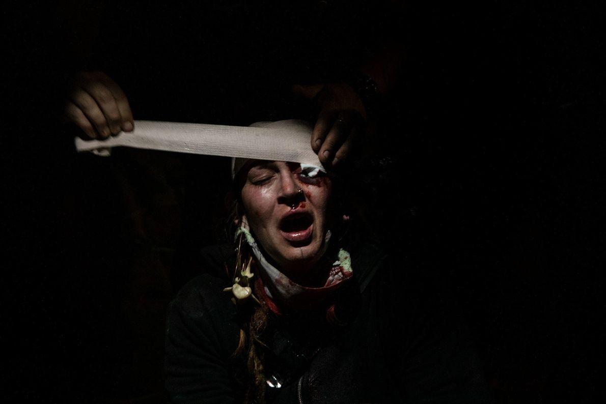 Una manifestante recibe primeros auxilios en el estacionamiento de una tienda. La policía le disparó una ...