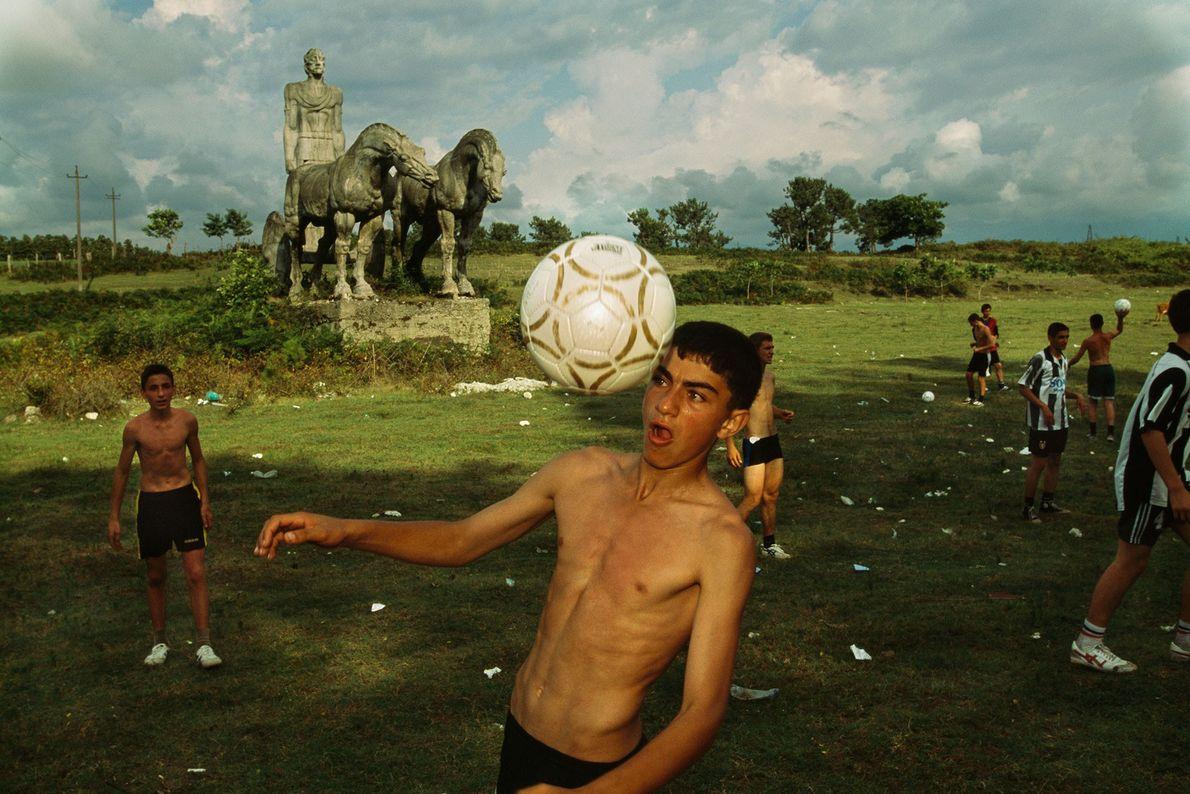 Un niño hace jueguitos con una pelota de fútbol mientras juega en un campo.