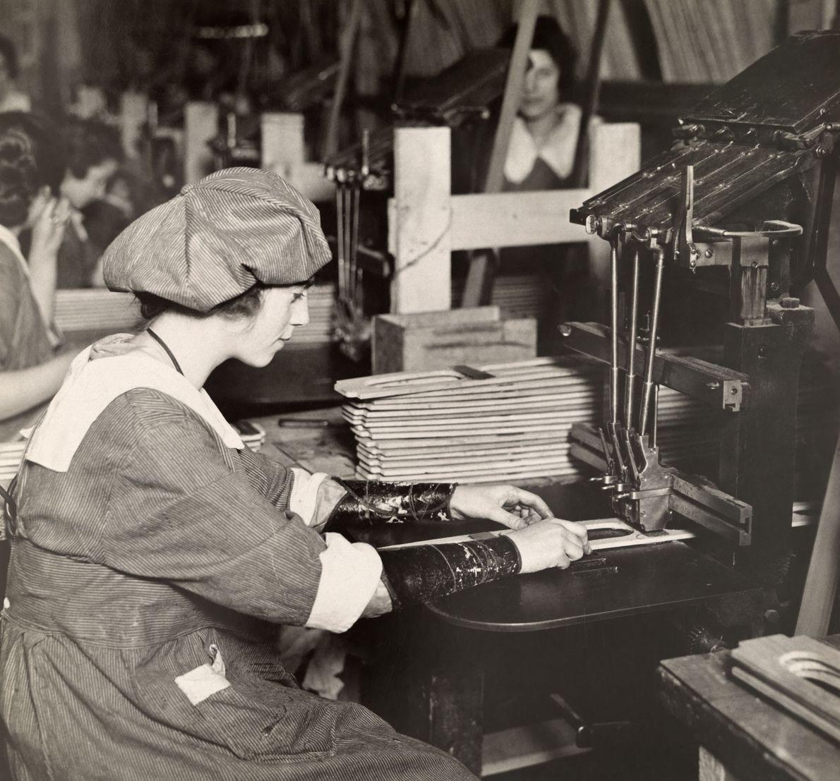 Una mujer trabaja en una punzonadora en una fábrica que fabrica piezas de aviones en los ...