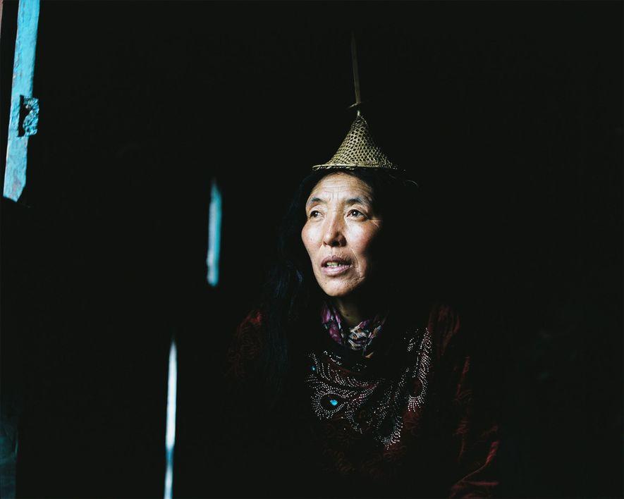 Lham, de 53 años, mira por la ventana de su casa en Laya.