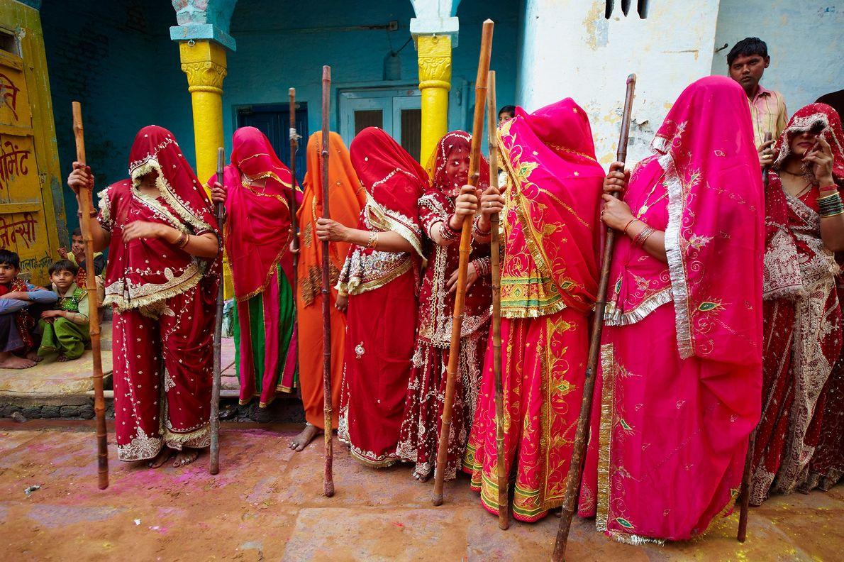 Durante el festival de Holi en Uttar Pradesh, India, las mujeres visten saris rojos tradicionales y ...