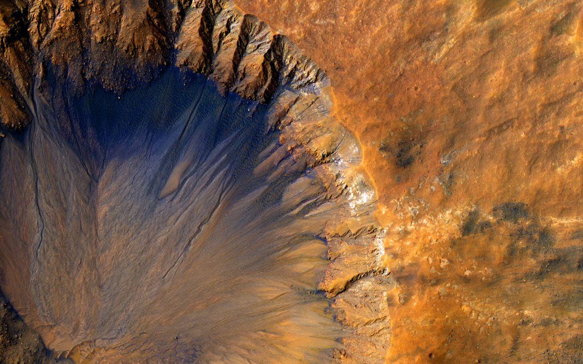 Este cráter cerca de Sirenum Fossae muestra laderas internas escarpadas llenas de surcos.