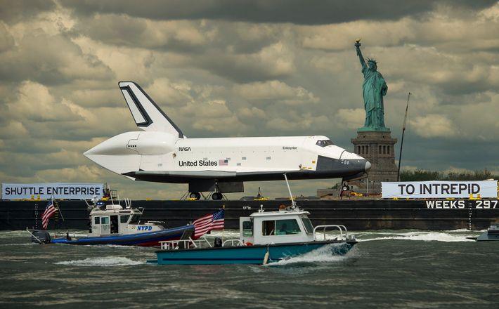 Ubicado en lo alto de una barcaza, el transbordador espacial Enterprise pasa por la Estatua de ...